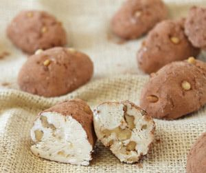 """These Irish Potatoes Candies are a smooth, divinity-based candy with a white chocolate flavor and loads of toasted walnuts. If you're familiar with the Irish Candy Potatoes from See's Candies, then this recipe will taste very familiar! The sweet potato look-alikes are rolled in a mixture of cocoa and cinnamon, and decorated with pine nut """"eyes."""""""