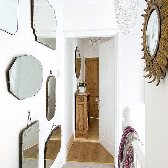 This small modern hallway is given visual character with a stunning display of vintage mirrors in all shapes and sizes.