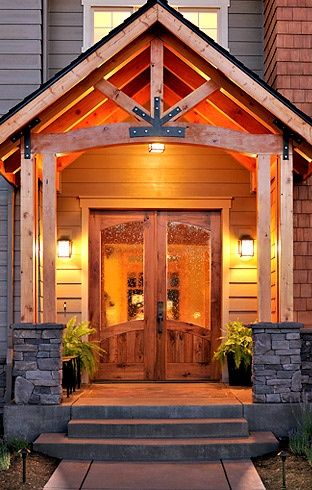 Love the portico accented with the black iron braces. Love the door with seeded glass and the stone foundation for the wood posts.