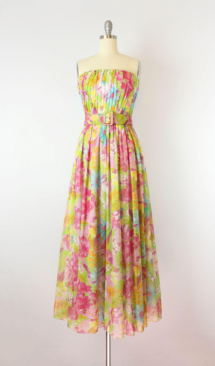 Vintage jaren 1950 floral print katoenen voile jurk. Strapless, uitgebeend bodice, die enigszins op de diagonaal is geplooid. Voorzien van taille en een top geplooide rok die in een vollere en vloeiende pasvorm door de heupen valt.  Gemaakt van een lichtgewicht en semi pure katoen die volledig bekleed is. Bovenlijfje heeft een witte nylon acetaat voering en de rok heeft een underlayer van paarse katoen / zijde mengsel. Metalen rits op de rug met verborgen module knoppen die de rok te ove...