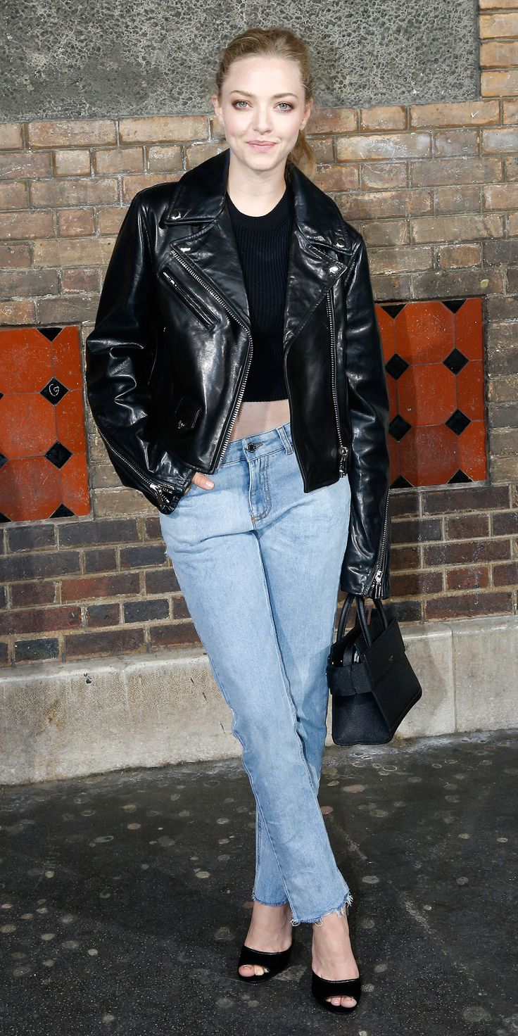 Amanda Seyfried in a Givenchy black crop top with high-waist straight-leg jeans and a tough moto jacket, putting it a ladylike spin with a darling top-handle purse and peep-toe pumps.