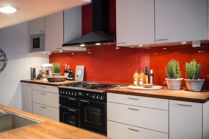 crédence de cuisine rouge, des armoires blanches et des appareils électroménagers noirs