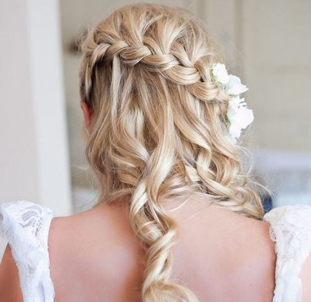 A beautiful waterfall braided hairstyle that looks amazing with a few fresh small flowers secured along the thick braid at the back. Soft curls that fall down the back completes this girl look.