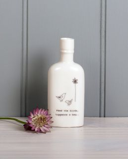 """A small porcelain bottle with dickie birds in the garden with the lyrics """"feed the birds, tuppence a bag"""" text from the musical Mary Poppins"""