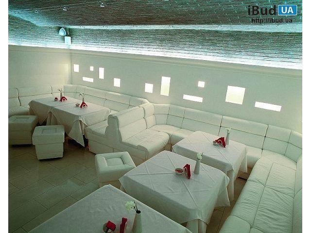 На фотографии показан дизайн интерьера ресторана в белом цвете. Помещение имеет необычный дизайн и стильный интерьер. Кирпичный потолок имеет неровную поверхность с разными изгибами. Для отделки ст...