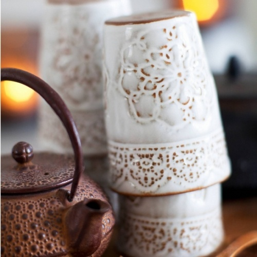 Handmade ceramic cup from Mia Blanche. It has Moroccan themed detailing all around the cup. This cup is glazed in a darker white than the other pieces from Mia and the clay is visible through the glaze.