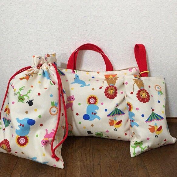 ◯レッスンバッグ◯シューズ袋○お着替え袋の3点セットです。賑やかなサーカス団のイラストがかわいいテキスタイル。春からの新生活を元気にスタートできそうですね。表地はオックス地を使用、裏地に生成り色の厚手シーチングを使用ししっかりしています(*^^*)お洗濯にも強くアイロンがけもしやすいです。◼︎サイズ◼︎◯レッスンバッグタテ30㎝ヨコ40㎝◯シューズ袋タテ27㎝ヨコ20㎝○お着替え袋タテ40㎝ヨコ30㎝多少の誤差はあります。ご了承くださいませm(._.)◼︎素材◼︎オックスシーチング(厚地)