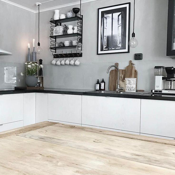 Białe szafki z czarnymi blatami w kuchni z drewnem