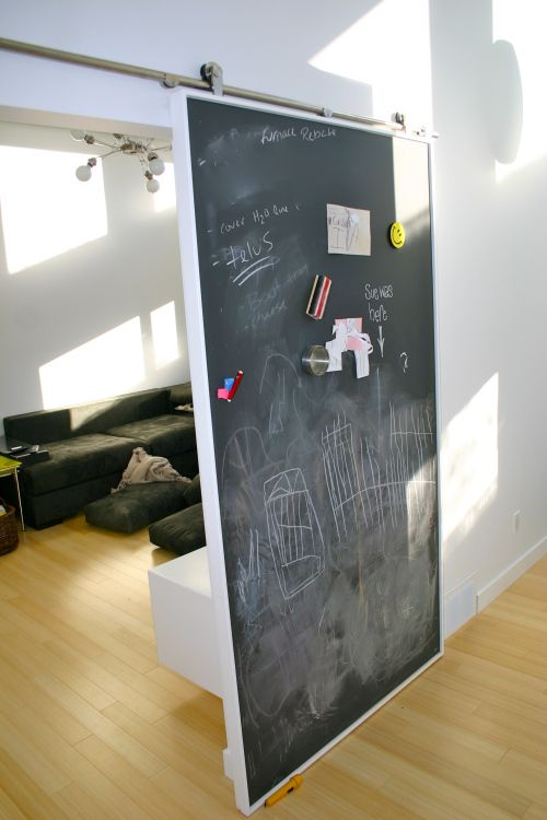 Sliding doors that we recently installed serve a dual purpose. One has a magnetic blackboard for notes and the kids to play on. The other set to the office/library allows for that space to be conne…