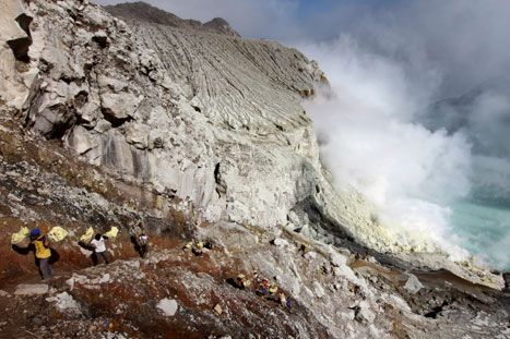 The sulphur miners have to creep down a narrow trail into the heart of the volcanic crater, Ijen Volcano, East Java, Indonesia