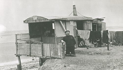 Charley Morgan, Selsey Beach. He lived in a caravan near Medmerry Mill. He had lost both his legs in an accident, but he continued to move about on the remains of his legs. He earned his living by doing odd jobs and dealing in horses. He died in May 1928. Charley is standing in front of a wooden hut entitled 'The Jubilee Restaurant' with clothing hanging out to dry.  Photo C 1910