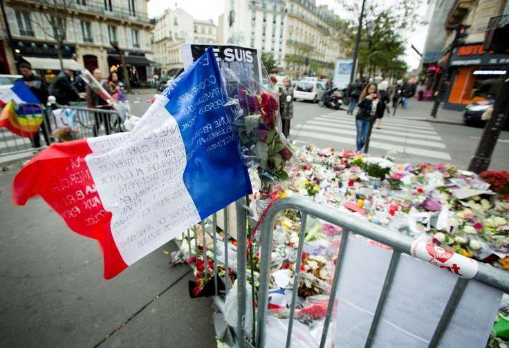 Een Franse vlag en bloemen en kaarsen in de buurt van Cafe Bataclan, een paar dagen na de aanslagen.