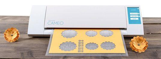 Silhouette CAMEO 2 – это универсальный настольный режущий плоттер от компании Graphtec. Он идеально подходит для вырезания изображений и текстов из бумаги, картона, винила и т.д. Эта модель крайне проста в эксплуатации и не требует специальных навыков. Она подключается к компьютеру как обычный принтер, но не печатает, а вырезает изображения из нужного материала специальным ножом.