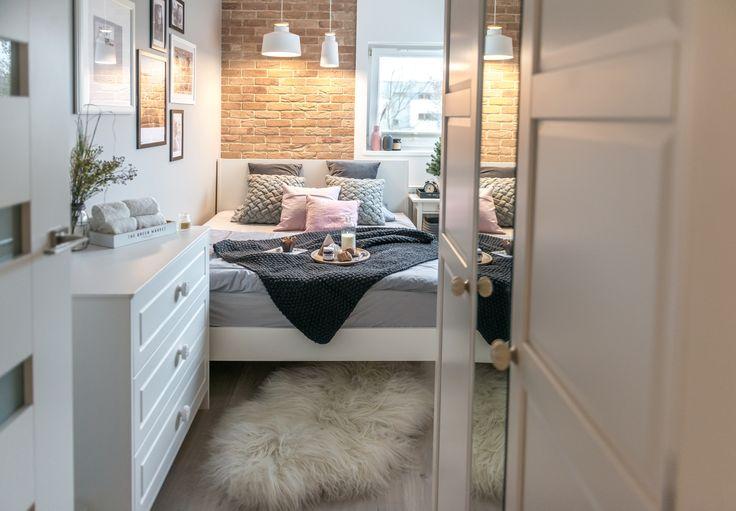Białe meble i czerwone cegły cegły w małej sypialni