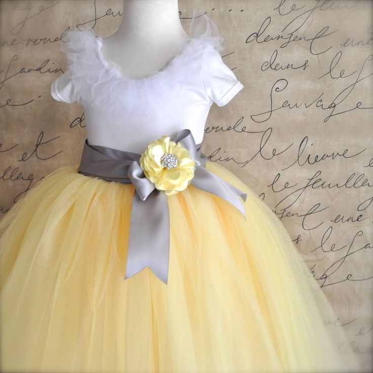 This girls tutu is a blend of yellow tulle with a silver grey satin ribbon waist. The tutu was photographed in a 20 length. Thank you to a wonderful bride for sending us her little Flower Girl photo who is modeling the yellow ribbon option! Choose any ribbon color from the pull-down menu. Flower clips in yellow or charcoal grey are available here: https://www.etsy.com/listing/188513170/satin-flower-clip-or-pin-with-large?ref=unav_listing-same Leotards are also av...