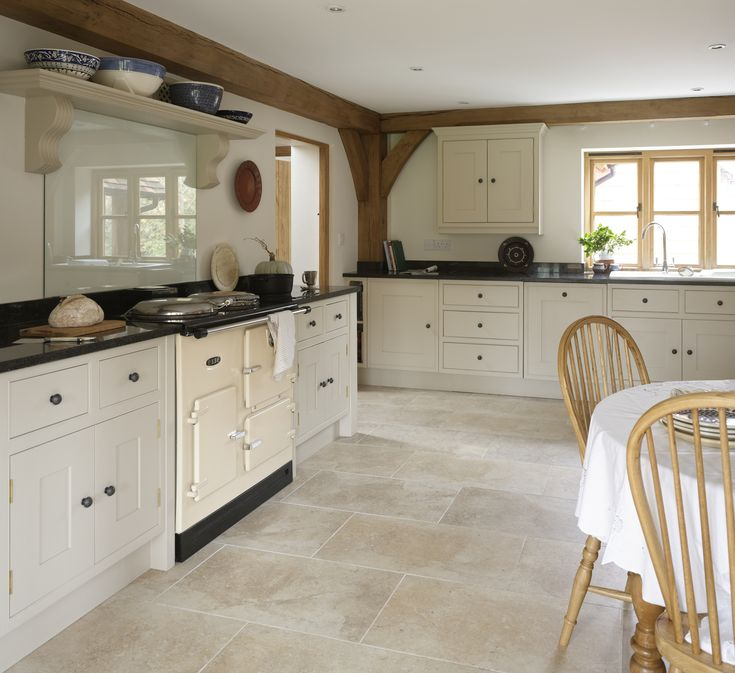 Painted kitchen with limestone floor  give this room a fresh, modern look. Love the combination of Aga and beams. http://www.thestonegallery.co.uk/natural-stone/range/limestone  Why not head on over to join our FREE interior design resource library at http://www.TheHomeDesignSchool.com/signup?
