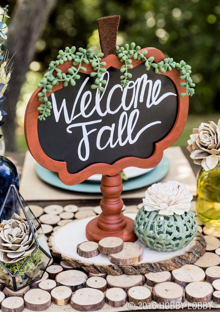 Welcome fall with a beautiful table setting! DIY the pumpkin chalkboard sign: 1) Paint frame & base of sign a fall color. Let dry. 2) Give the sign a distressed look by brushing over the paint. 3) Cut stem out of brown felt & attach using hot glue. 4) Place strands of the succulent on the chalkboard sign using hot glue.  DIY the wood disk runner: 1) Take a pre-made runner (we used burlap) & iron it. 2) Arrange mini wood disks on your runner. 3) Hot glue wood disks until your runner is…