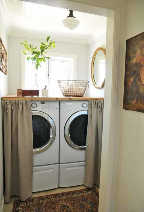 A butcher-block slab morphs the top of your machines into usable workspace. Plus, pull the cute curtains, and your utility room is suddenly just cozy nook. It's a clever trick for holiday party season — washing machines aren't exactly festive. Click through for more on this and other tips for small laundry room organization.