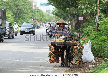 HANOI, VIETNAM - JUNE 28, 2014: Unidentified fruit vendor selling pineapple on a…