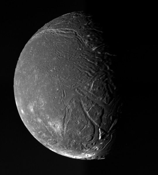 Titania, moon of Uranus, is photographed by the Voyager 2 space probe on January 24, 1986, from a distance of 229,000 miles.