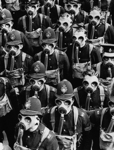 "London policemen (""bobbies"") wear gas masks for a training drill. September 1937.    Haunting image...."