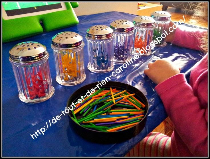 Insérer des allumettes colorées dans un contenant pour développer la moticité fine et la coordination visuo-motrice