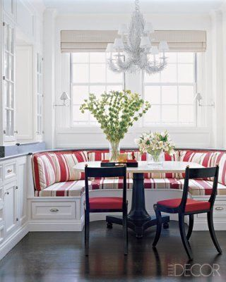 the red stripe, the banquette with its storage drawers, the black of the chairs & table base against all the white ... I love it all.