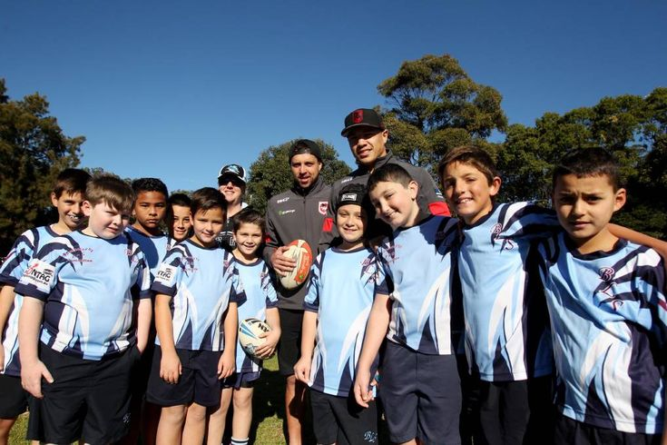 We love our footy: Brighton-Le-Sands Public School teacher Julie Bernhardt (left, back),  Dragons players Gerard Beale and Tyson Frizell, and the students at Carss Park on Friday. Picture: Chris Lane