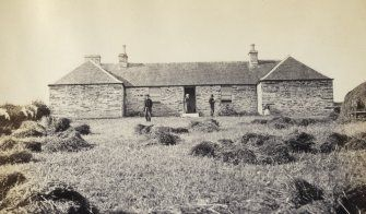 View of front of the school at Kilchattan with three adult figures and small child, on Colonsay, Argyll.  Titled: 'School, Kilchattan, Colonsay'.  PHOTOGRAPH ALBUM No. 187, (cf PAs 186 and 188) Rev. J.B. MacKenzie of Colonsay Albums,1870, vol.2.