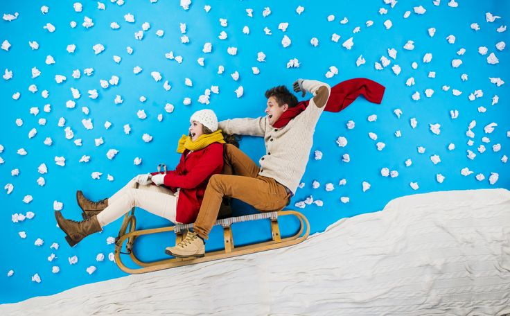 Young couple on sledge having fun - Happy young couple on sledge having fun against the blue background with snowflakes