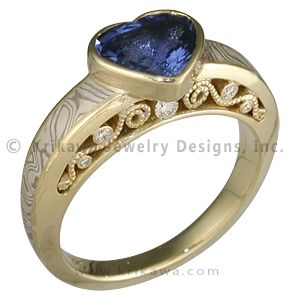 Heart Shaped Blue Sapphire in Mokume Curls Engagement Ring - Five accent diamonds, 0.15 ctw, are nestled in elegant millegrain curls on each side of this unique engagement ring. The mokume body tapers away from the inside of the ring to reveal the side detail. A brilliant cut diamond is set in low profile by a semi-bezel with millegrain detail. 5mm wide. Ideal cut accent diamonds.   - This custom designed mokume engagement ring is set with a heart-shaped blue sapphire. An 18K yellow gold…