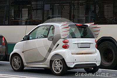 White subcompact with decorative elements in the rear part in the shape of wings of sandals of Hermes, standing in a traffic jam on the asphalt road at the side of the bus. View from the left side and rear. Closeup