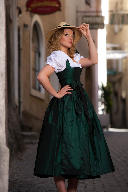 dark green dress - almost looks like a traditional German dirndl - green brocade mid calf length sleeveless wide strap dress, short puffed sleeve white blouse, straw hat