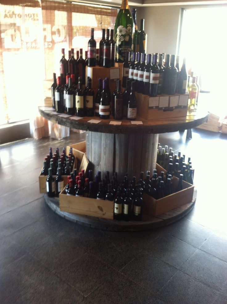 Electrical wire spool used as wine display table at Cru Cellars in Tampa, FL