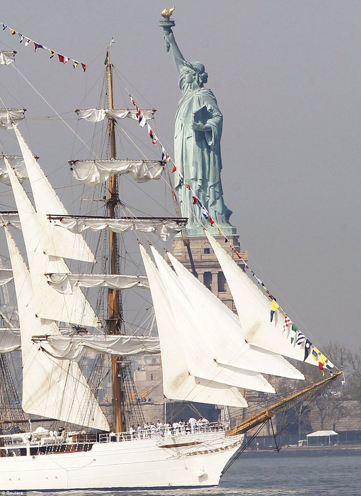 The tall ship Cisne Branco (White Swan), a Brazilian Navy ship, passes the Statue of Liberty in New York Harbor while arriving for the 25th annual Fleet Week celebration in New York on Wednesday