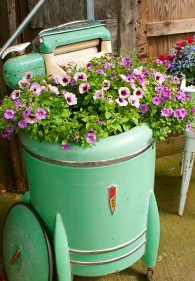 I've seen so many different antiques being used in gardening.  This picture makes me wish I had kept my Mother's old wringer washer, among some other things -- because the lesson in junk/antique gardening is simple….if it can hold soil, it will make a pretty planter.
