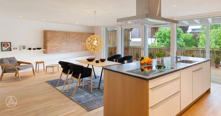 Einladender Essbereich mit offener Küche. Die bodentiefen Fenster machen den großen Raum hell und freundlich. Baufritz Mehrfamilienhaus Uetendorf.