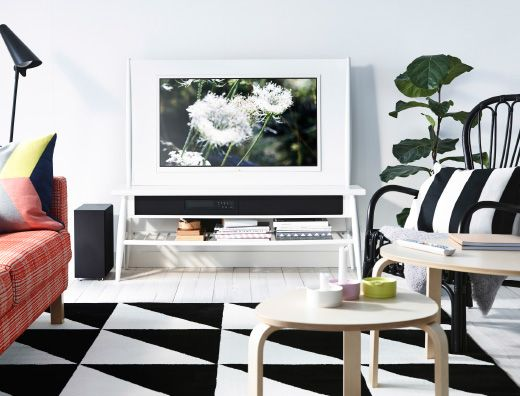 Hvit stue med UPPLEVA HIMNA TV i hvit, KARLSTAD oransje sofa og IKEA PS 2014 rutemønstret teppe