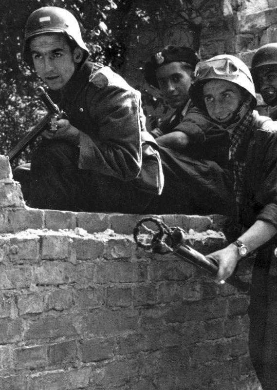 Польский повстанец-огнеметчик с товарищами на улице восставшей Варшавы