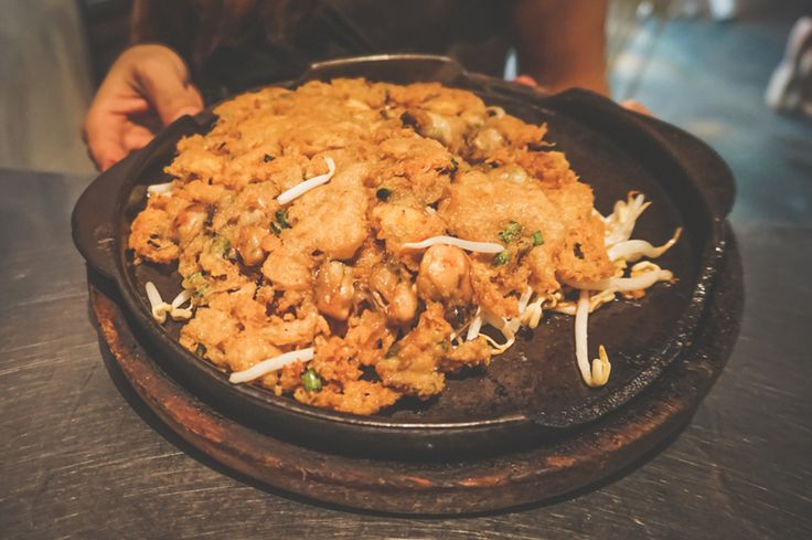 Crisp fried mussel pancake is cooked in large frying pan and it is fun to watch the dish cooked.