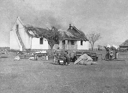 Boer civilians watch as their house burns from scorched earth tactics by the British Army during the Second Anglo-Boer War, South Africa, 1899-1902.