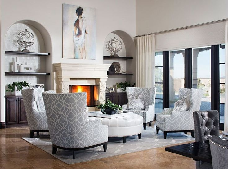White and grey feature throughout this high ceiling living room, with four high back chairs pivoting around immense white leather circular ottoman. Marble fireplace is flanked by dark wood cabinetry and shelving, with sliding glass door to patio on right.