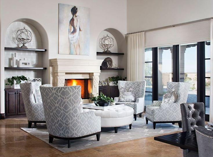 Blanca y característica gris largo de este alto salón de techo, con cuatro sillas de respaldo alto pivotando alrededor inmensa otomana de cuero blanco circular.  Chimenea de mármol está flanqueado por armarios de madera oscura y estanterías con puertas correderas de cristal al patio a la derecha.