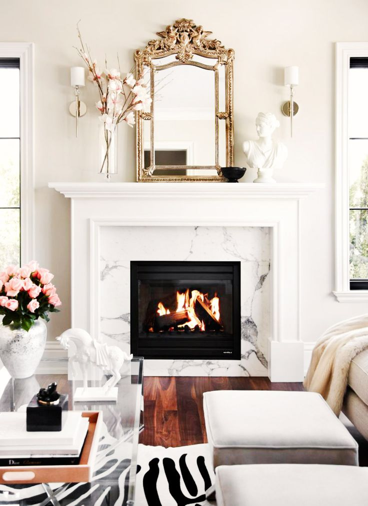 Marble fireplace with gold mirror resting on top: