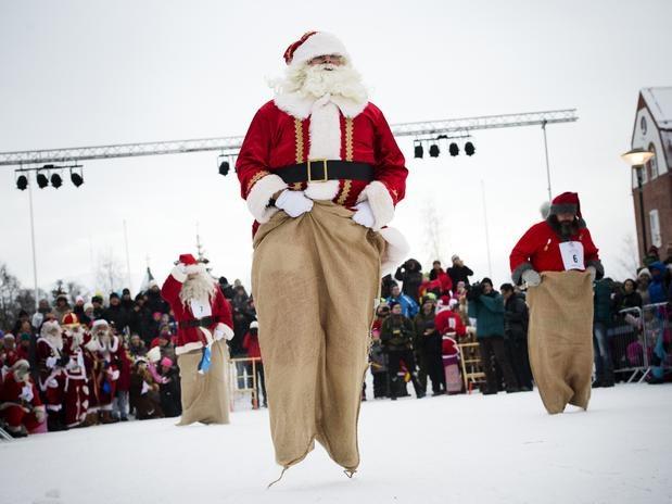 """18-nov-2012 - GALLVARE - LAPÔNIA: Papais Noéis competiram em corrida de saco durante os """"Jogos de Inverno de Papai Noel"""" em Gallvare a 100 Km ao norte, do Circulo Polar, onde """"Santa's"""" de todo o mundo se reunem para participar dos Jogos. """"Vamos ficar em forma antes de começar a distribuir os presentes e fazer a alegria das crianças""""! Antes da competição, para a alegria dos moradores, todos os """"Santa's"""" passeiam pela cidade com seus assistentes, elfos e duendes... Foto: AFP."""