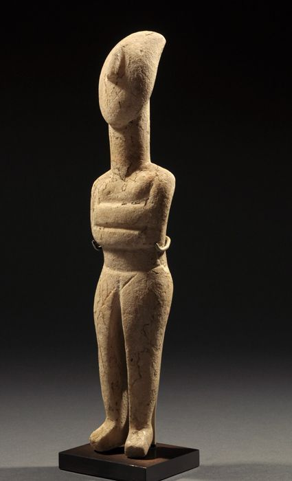 Cycladic marble idol of a reclining female, early Spedos type, Early Bronze Age II, 2600-2500 B.C. Stylized nude figure, arms are folded beneath breasts, slender lyre shaped nose and long oval neck, incised details with traces of red pigment and strong root marks. The vast majority of these striking Cycladic idols are female and some archaeologists believe that they express supplication or prayer because their faces look upward, 24.6 cm high. Private collection