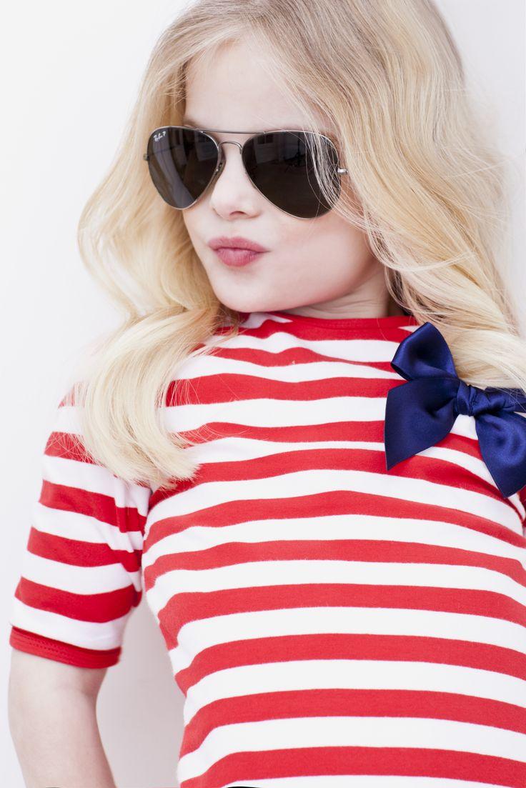 Dit rood-wit gestreepte jurkje is heerlijk voor naar het strand of om 's avonds te flaneren over de Zuid-Franse boulevards. Met korte mouw voor de warme dagen maar ook leuk met een spijkerjasje of donkerblauw vestje als het wat frisser is. Het witte ceintuurtje is vastgestikt in de zijnaad en kun je zowel voor als achter strikken.