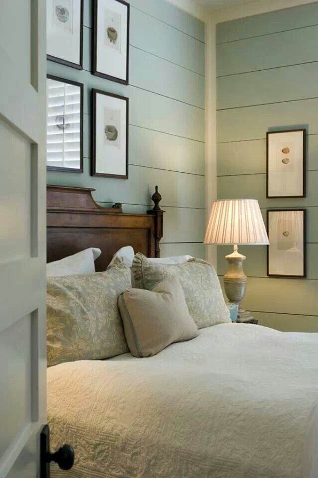 Bedroom with aqua ship lap walls, bird nests and egg prints, dark wood bed, and white coverlet.