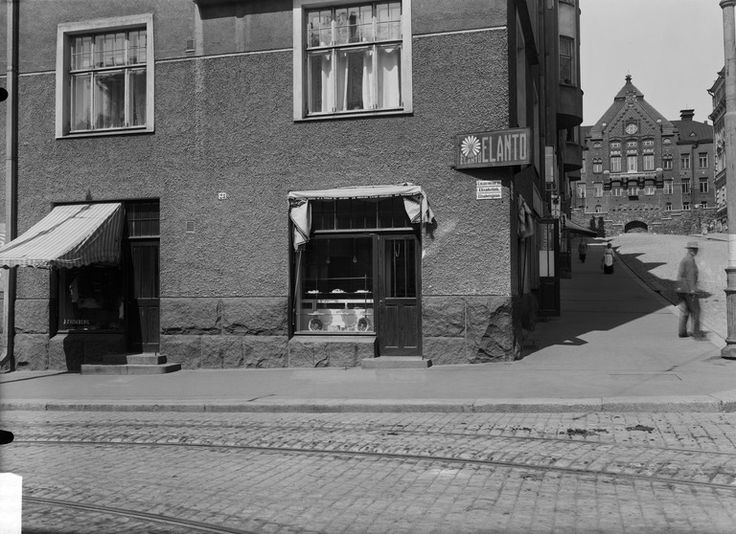 Elannon leipä- ja maitomyymälä n:o 5. Elisabetinkatu 23 (- Nikolainkatu 16, = Liisankatu 23 - Snellmaninkatu 16) . Taustalla on Siltavuorenpenger 20 ( piirtänyt G. Nyström).   Tuntematon 1915   Helsingin kaupunginmuseo   negatiivi, lasi, mv