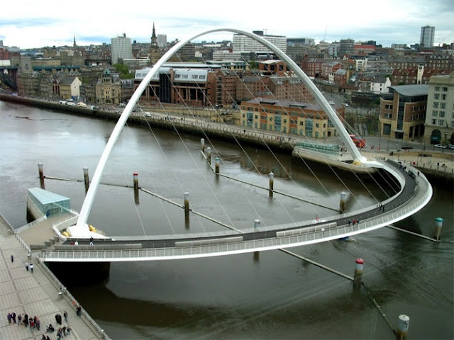 Gateshead Millenium Bridge (Gateshead, England)...  The Gateshead Millennium Bridge is a pedestrian and cyclist tilt bridge spanning the River Tyne in England between Gateshead's Quays arts quarter on the south bank, and the Quayside of Newcastle upon Tyne on the north bank...